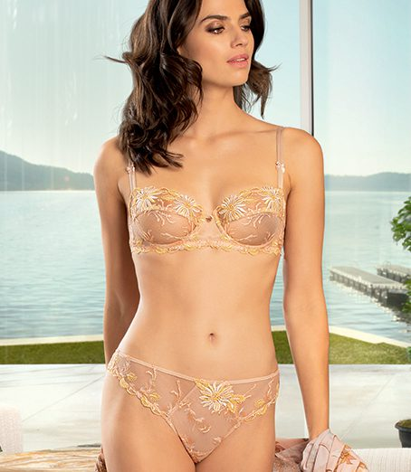 Woman wearing Lise Charmel Fleur Aphrodite underwired balconnet bra in skin colour with matching brief